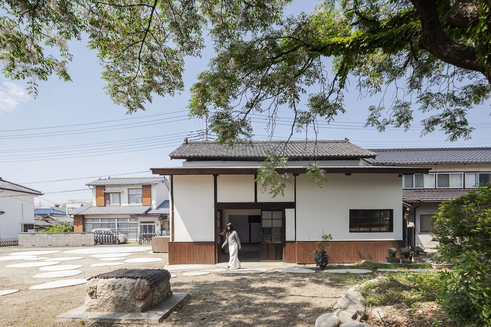 Exterior, House Building Type, Tile Roof Material, and Wood Siding Material New circular plinths, a nod to stepping stones found in Japanese gardens, surround the structure to activate the vacant areas of the building lot.  Photo 8 of 8 in Saved From Demolition, a Japanese Sake Warehouse Sees a Second Life