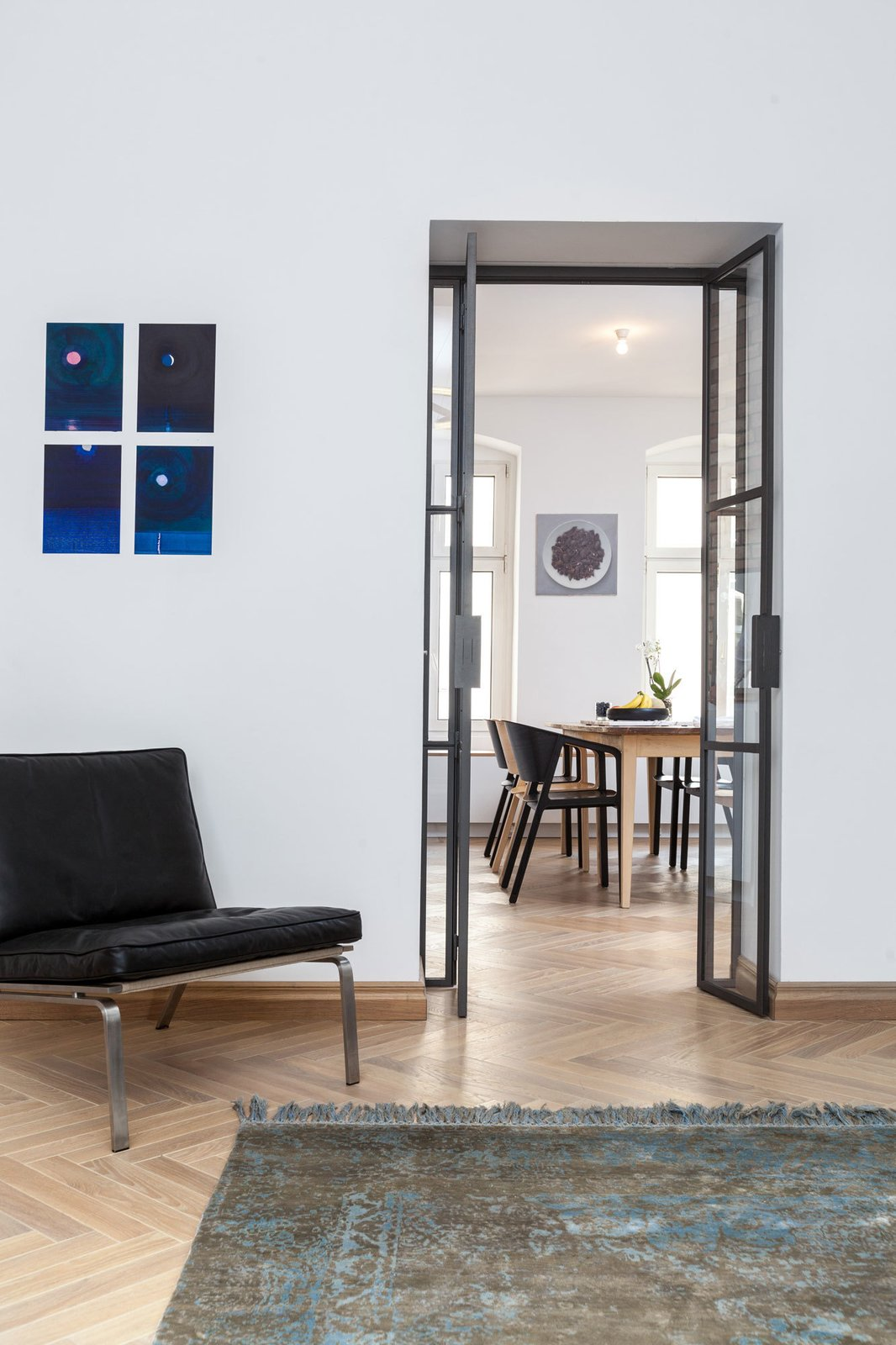 A new custom glass door separates the living room from the kitchen and dining area while allowing natural light to filter through.  Photo 4 of 7 in A Hidden Passageway Makes Each Room in This Berlin Flat a Private Destination