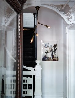 Carefully placed modern touches illuminate restored details in the home. An industrial-style pendant, which Jeff and Jason created themselves using a DIY instructional kit by lighting designer Lindsey Adelman, hangs from the intricate millwork in the entryway. The print is by photographer Anna Wolf.