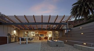 """""""The rear yard, given the property's limited size, presented more of a conundrum,"""" says Southerland. """"We came up with the idea of using the roof of the garage as a roof deck to add useable area to the rear."""" Taking advantage of the gently sloped site, he built a series of terraced bleacher-style seating above and around the detached garage, doubling its roof as an additional terrace, and effectively bridging the backyard space into one multi-level whole."""