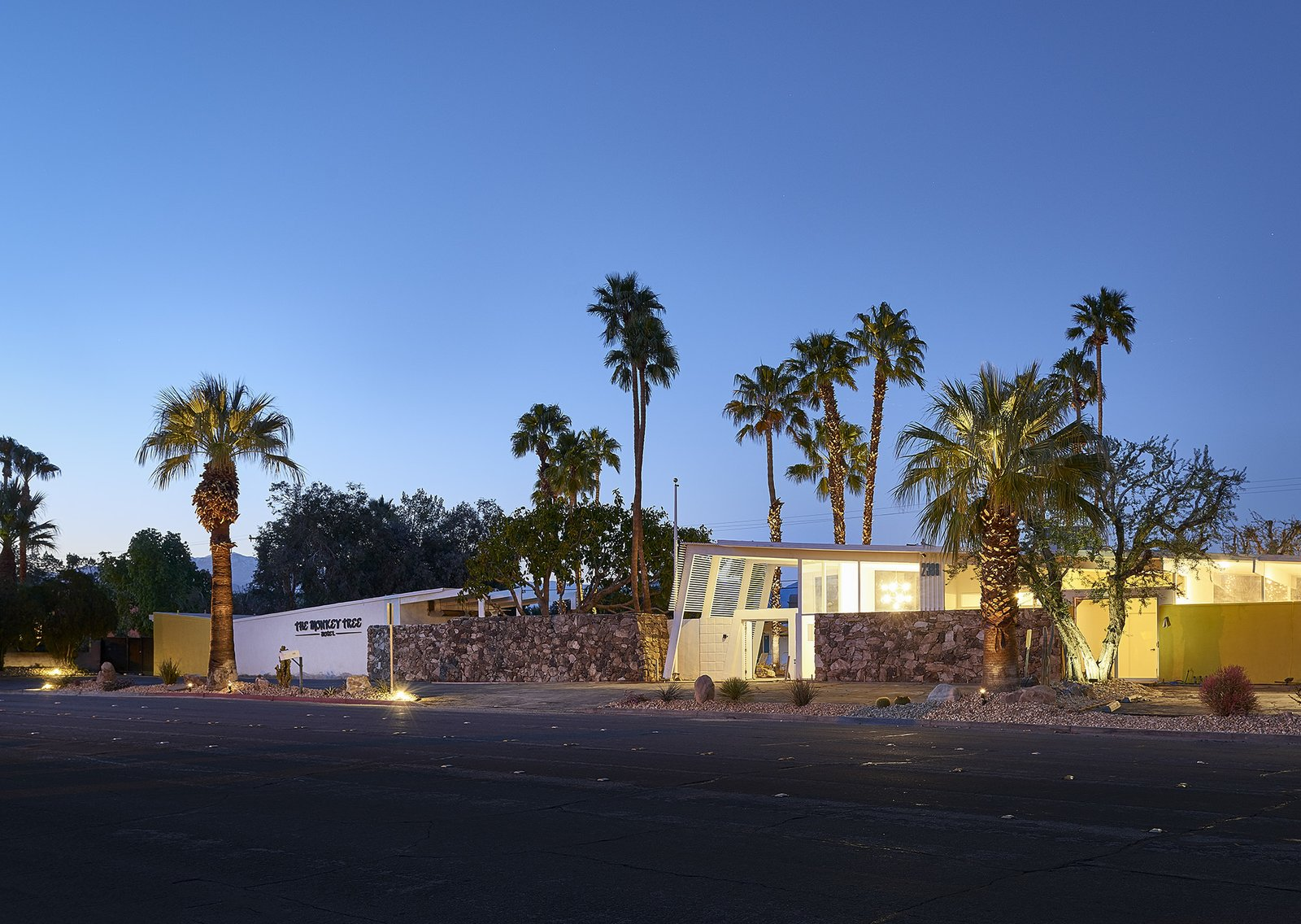 """Exterior, Stone Siding Material, and Mid-Century Building Type To recreate that 1960s flair Kathy, a designer, spent four months scouring for vintage treasures. """"Because we were buying a Palm Springs midcentury modern hotel, I wanted to furnish it with pieces that made sense and were true to that time period,"""" Kathy says. """"That said, I wasn't too strict."""" That means guests may find an '80s chrome coffee table or Jonathan Adler seconds alongside macrame wall hangings and Gainey pots.   The Monkey Tree Hotel from This Palm Springs Hotel is Filled with Vintage Midcentury Modern Finds"""