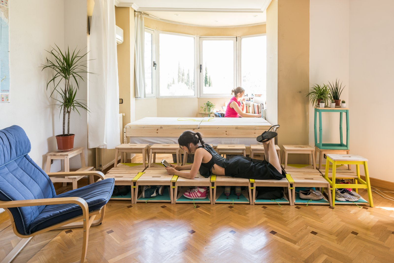 Living Room, Chair, and Medium Hardwood Floor To create a temporary bedroom and study space for a PhD student, ENORME used simple components provided by IKEA.  Best Photos from Reinventing the Family Home for the Boomerang Generation