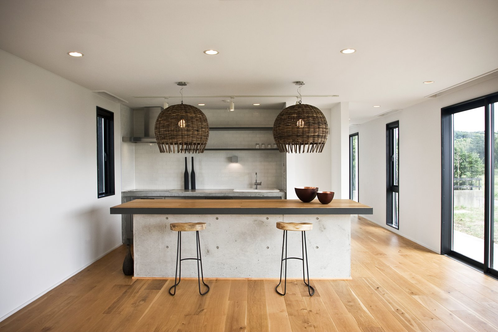 Kitchen, Pendant Lighting, Medium Hardwood Floor, and Wood Counter The kitchen island is made of concrete with an oak top and black steel edging—an industrial element within a project that celebrates nature.  Photo 6 of 7 in This Minimal Japanese Getaway Was Built for Surfing