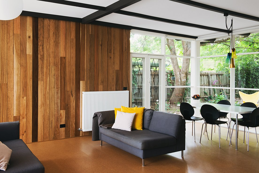 Living Room and Sofa Timber clad walls meet cork flooring in the open living room at the center of the home.  Best Photos from An Australian Renovation Gives New Life to Midcentury Style