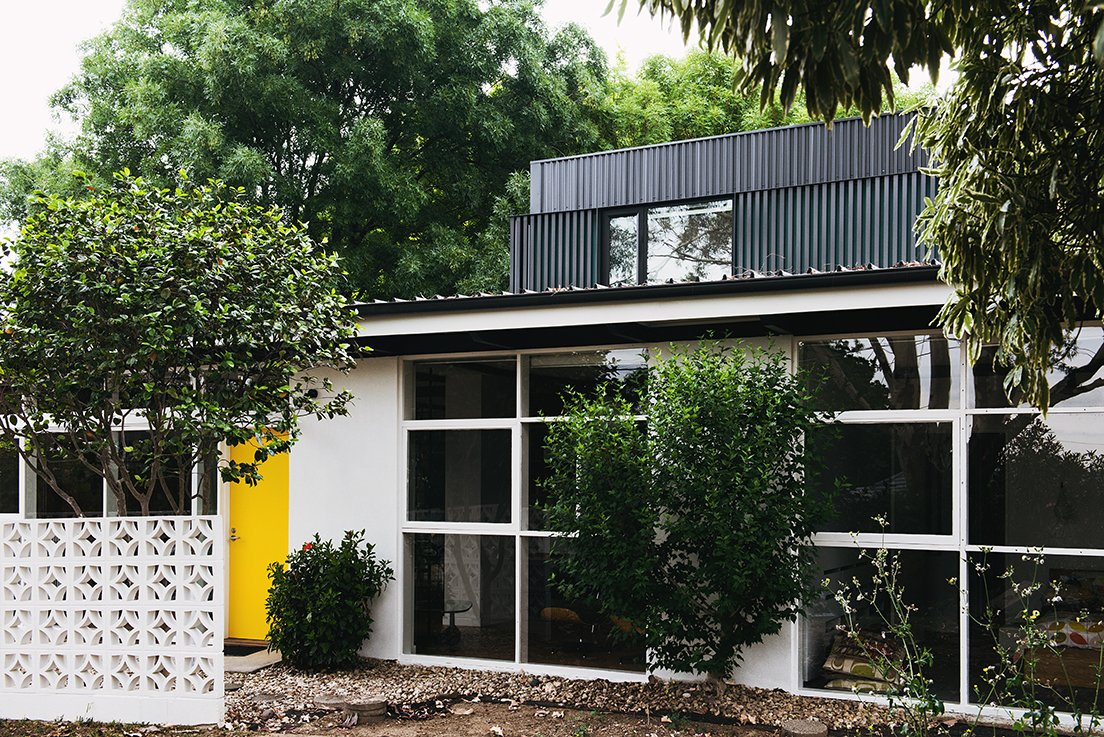 Exterior, Metal Siding Material, Stucco Siding Material, and House Building Type When tasked with renovating a house near Melbourne, the team at Nest Architects decided to honor its midcentury bones while modernizing it for today's residents. The yellow hue on the front door is a detail picked up from the original design.  Best Photos from An Australian Renovation Gives New Life to Midcentury Style