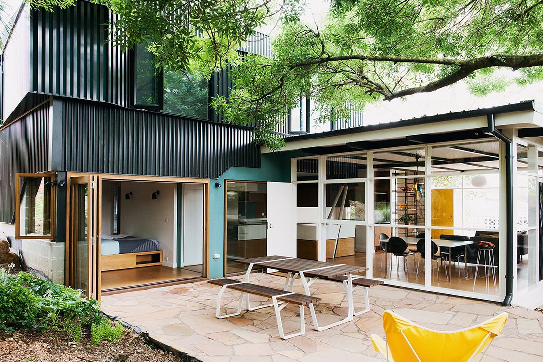 Outdoor, Stone Patio, Porch, Deck, Back Yard, and Small Patio, Porch, Deck The result is a multipurpose living area that opens up to an exterior courtyard anchored by a Ross Gardam Flint table.  Modern Landscaping from An Australian Renovation Gives New Life to Midcentury Style
