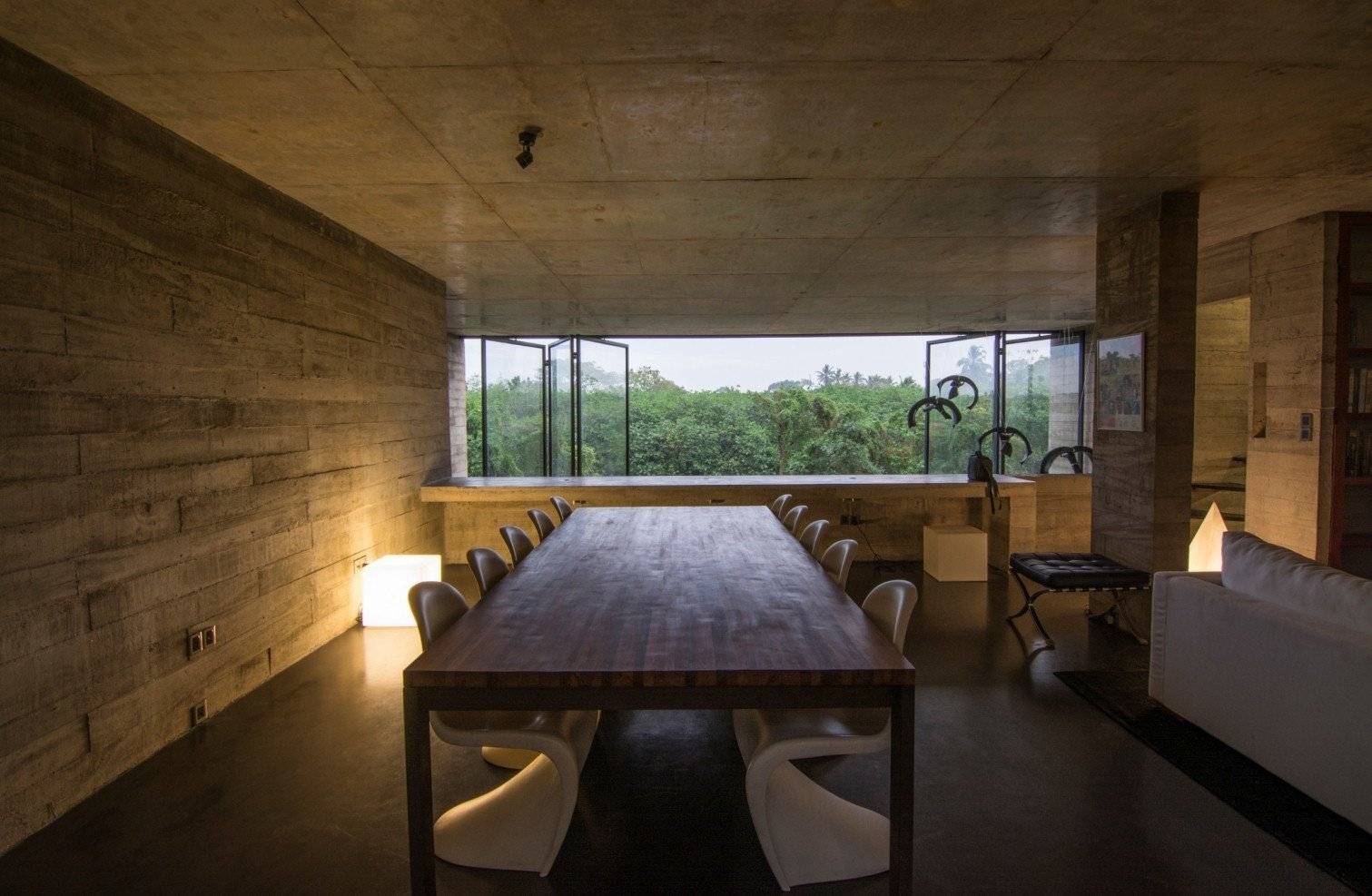 Dining Room, Table, Chair, and Floor Lighting Expanses of low-e glass open to views of the nearby greenery.  Best Photos from An Architect's Home and Studio Rises Above Rajagiriya