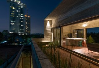 A roof deck offers views of both the city and the surrounding marsh. The roof's biological ponds regulate stormwater, while its edible herb gardens and paddy fields help to keep the interior of the home cool despite the tropical heat.