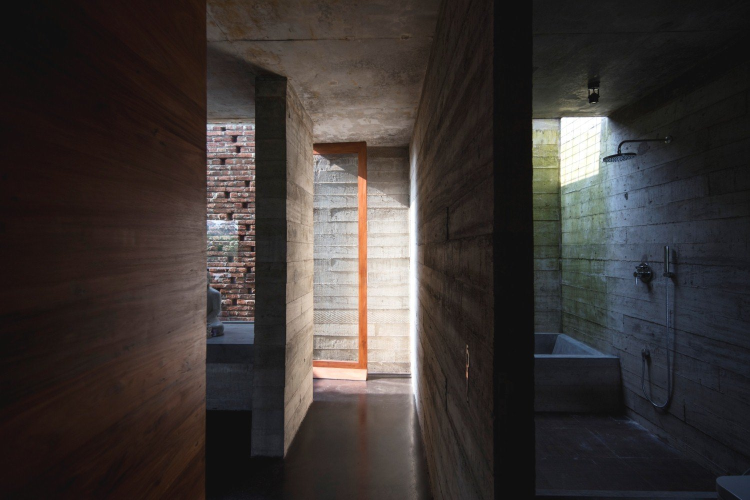 Bath Room, Open Shower, Concrete Wall, and Concrete Floor Brick and board-formed concrete are the primary materials of the rugged, yet elegant, structure.  Photo 6 of 7 in An Architect's Home and Studio Rises Above Rajagiriya
