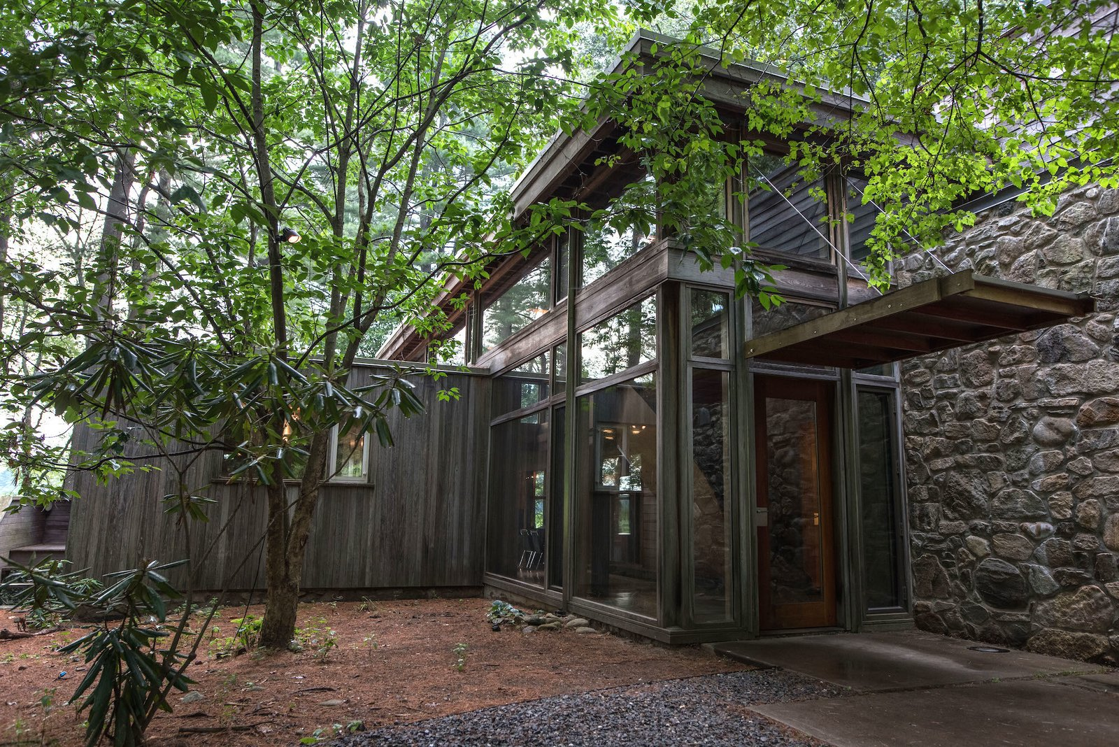 Exterior, Wood Siding Material, and House Building Type A glass-walled addition joins Marcel Breuer's minimalist Chamberlain Cottage. Part of the original house extends from the left of the structure.  Photo 4 of 4 in This Updated Breuer House Could Be Yours for a Cool $2.3 Million