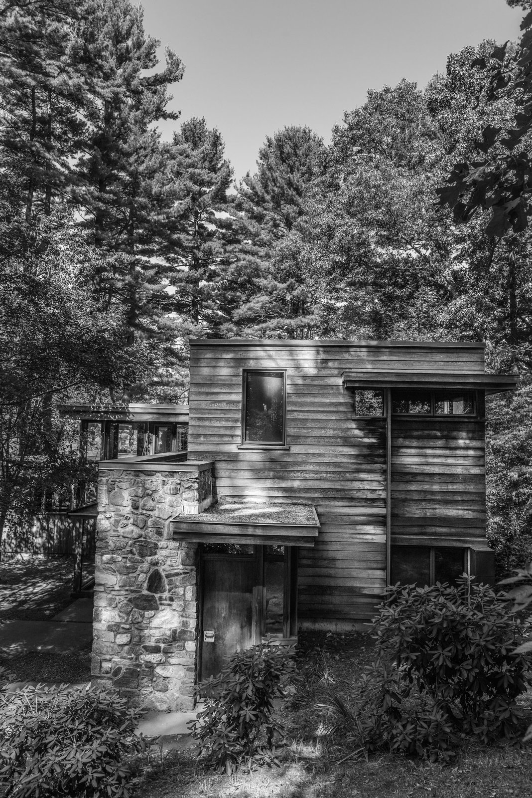 The stone and wood structure was designed to complement with its surroundings. Here, the Douglas fir tongue-and-groove boards are arranged horizontally, elsewhere on the original facade they were aligned vertically.  Modern Marvels from This Updated Breuer House Could Be Yours for a Cool $2.3 Million