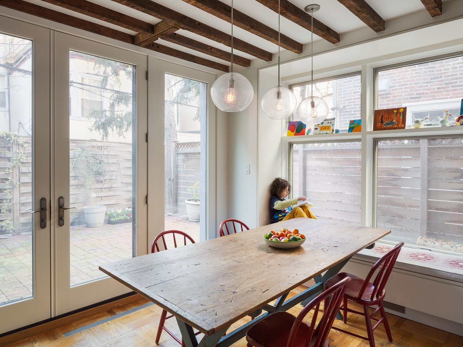 Dining Room, Table, Pendant Lighting, Chair, and Medium Hardwood Floor Dark beams contrast the glazing that fills the dining area with light, continuing the home's historic/modern mix.  Photo 6 of 9 in Philadelphia Row House Renovation