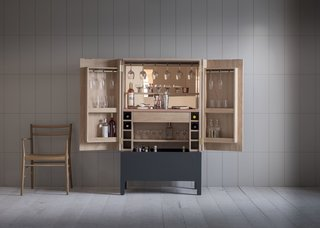 The Frans drinks cabinet, which Pinch showcased at Decorex International during the London Design Festival, features a satin copper lacquered work surface, adjustable shelves to allow for varying bottle and glass heights, a stained and silicon-lined drinks trough, space for wine storage, and space for hanging glasses.