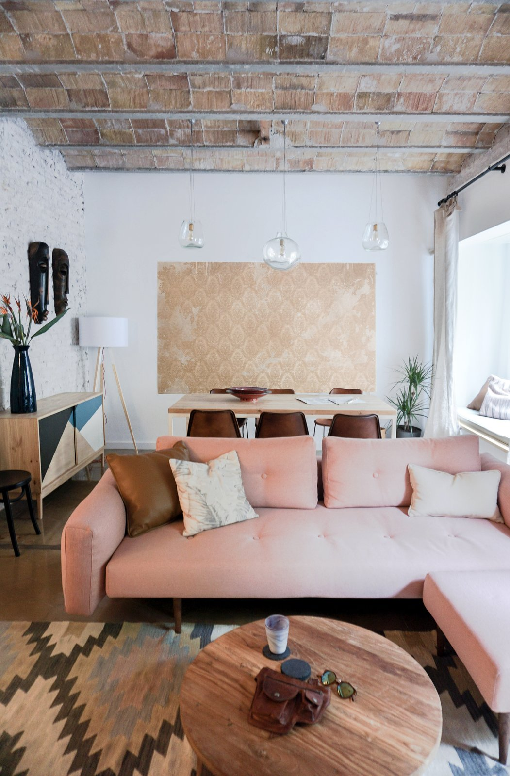 To make the space feel brighter, all of the walls—even bricks—are painted white, which contrasts with the raw brick ceiling and original brown tile floors. The Recast Plus sofa bed, with a pink hue that echoes the brick ceiling, is from Innovation Living. The blown-glass Gordiola pendants are a design the resident saw in a Mallorca hotel that Bloomint designed. Tagged: Living Room, Sofa, Ceramic Tile Floor, and Pendant Lighting.  Photo 2 of 9 in A Barcelona Apartment Gets a Softly Modern Renovation