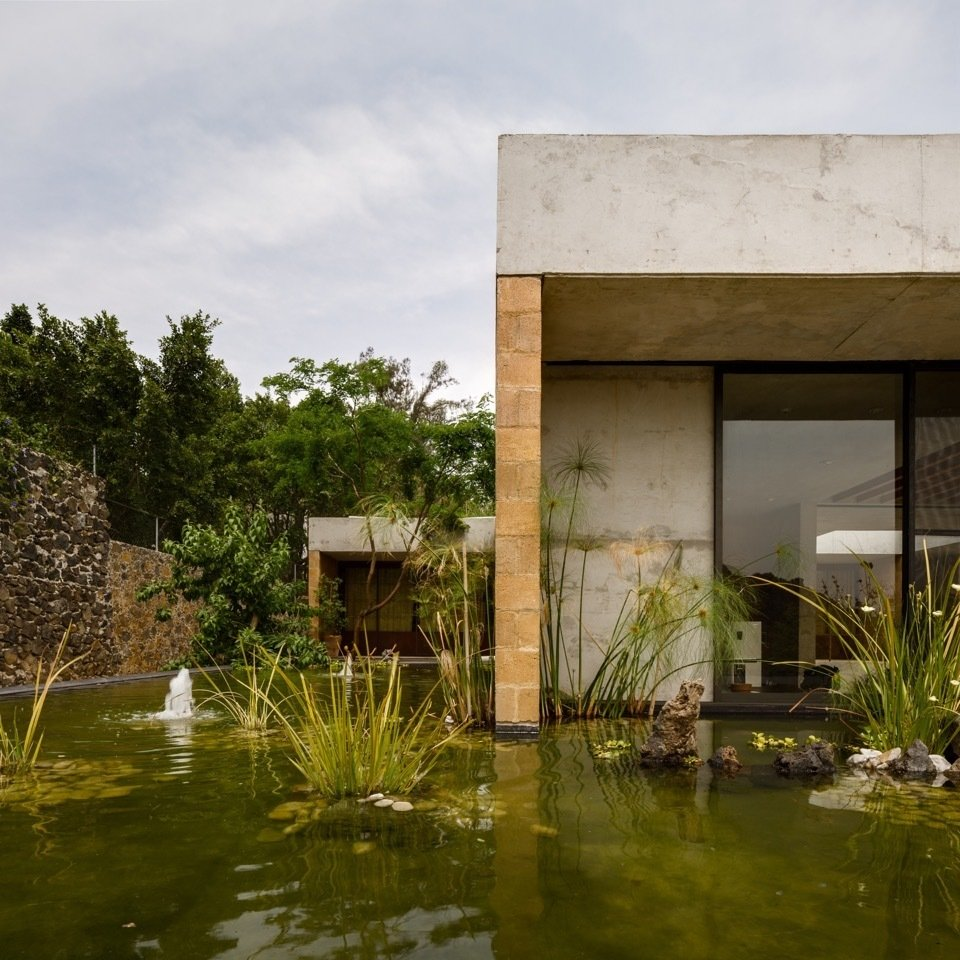 Exterior, Concrete Siding Material, and House Building Type Located outside of Mexico City, Casa GP by architecture firm Ambrosi | Etchegaray integrates the local landscape with features like this pond.  Photo 2 of 8 in An Eco-Friendly Getaway Built With the Future in Mind