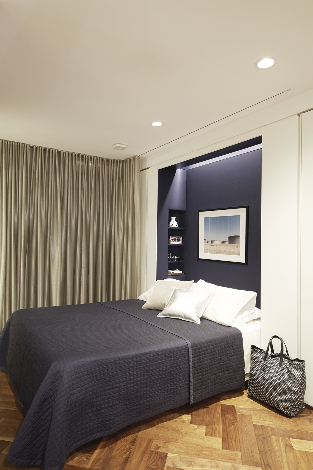 Bedroom, Bed, Medium Hardwood Floor, and Recessed Lighting The Murphy bed niche is lined in deep blue fabric by Knoll.  Best Photos from In Just 450 Square Feet, A New York Architect Crafts a Multifunctional Apartment of His Own