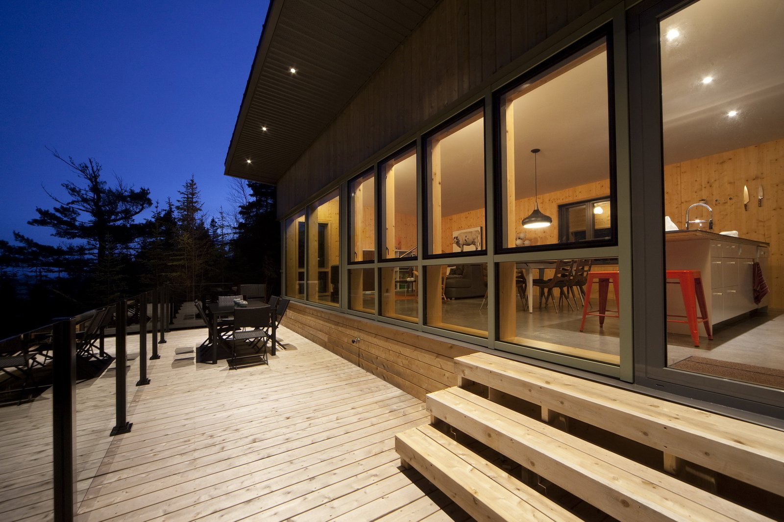 The home is conceived as a single, level volume, safe for a deck and outdoor dining area located a few steps below the indoors.  Photo 4 of 4 in The St. Lawrence River Flows Right by This Cottage's Doorstep