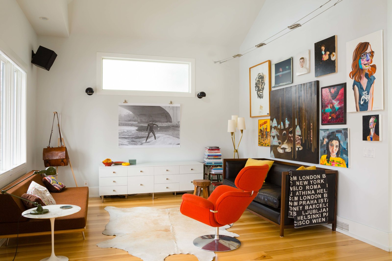 Lori Andrew and Ken Corner continue to add furniture to their Calgary, Alberta, home. The black leather Montauk sofa was the first piece Lori ever bought; the orange Pierre Paulin Tulip lounge chair was a birthday gift to Ken.  Habitats from This Century-Old Bungalow Is an Eternal Work-in-Progress