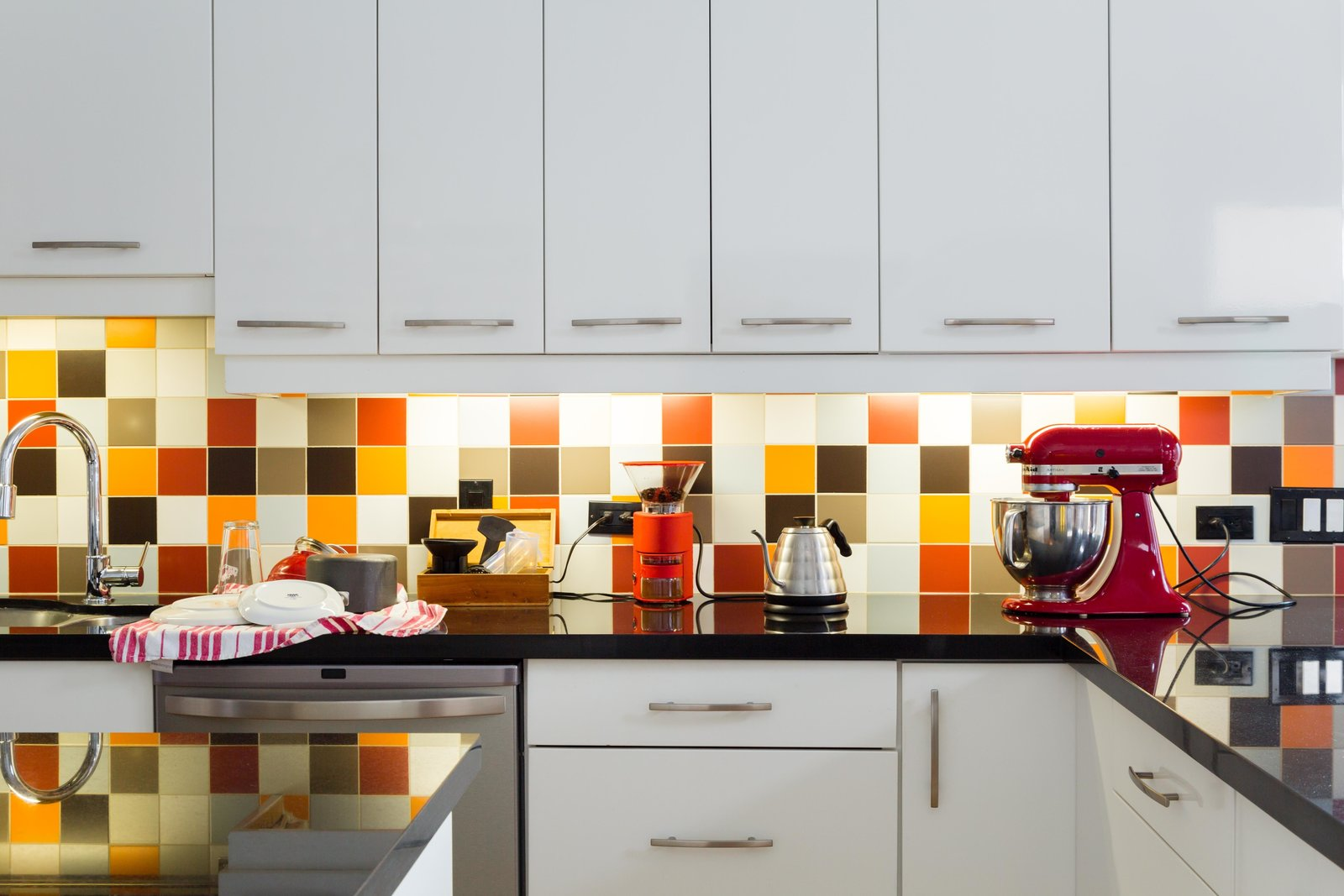 A patchwork of multicolored tile form an exuberant backsplash in the kitchen.  Photo 3 of 5 in This Century-Old Bungalow Is an Eternal Work-in-Progress
