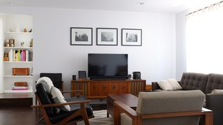 The living room is outfitted with a Petrie sofa from Crate & Barrel and a leather love seat from Room & Board. The armchair and console are vintage.