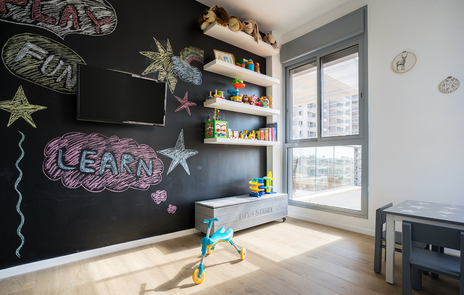 Kids Room, Bedroom Room Type, Shelves, and Light Hardwood Floor A chalkboard wall encourages creative exploration in the child's room.  Photo 4 of 4 in A Riotous Makeover for a Generic  High-Rise Home