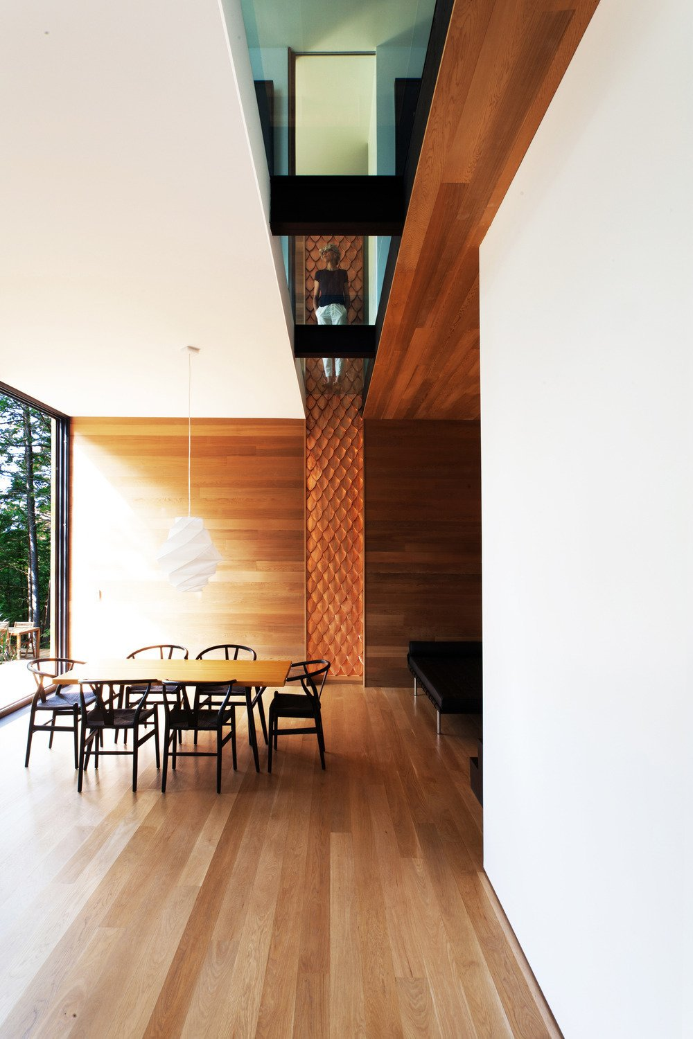 Dining Room, Chair, Table, Pendant Lighting, and Light Hardwood Floor A textured wood walls meets a glass cutaway on the second floor. The Wishbone chairs are by Hans Wegner.  Photo 2 of 5 in Is it Any Surprise a Sculptor Had a Hand in This Home?