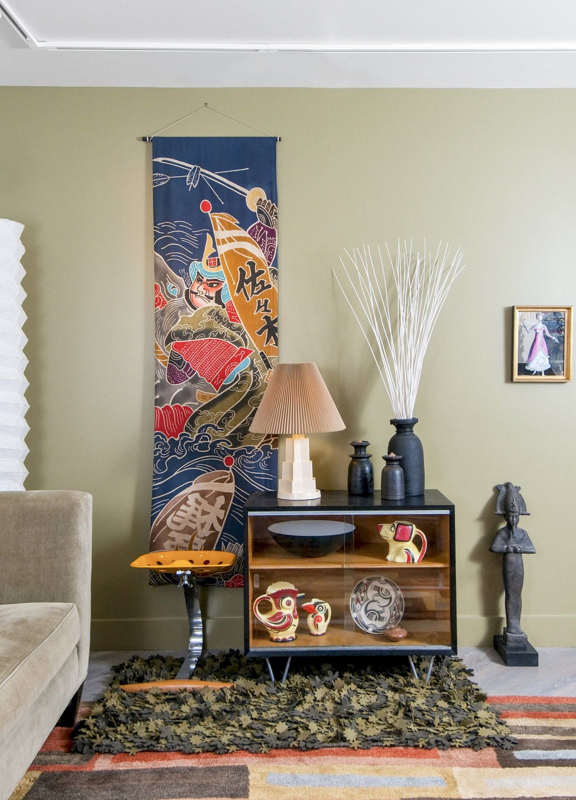 A living room vignette includes a 1950s batik Boy's Day banner from Japan, Czech pottery, and a framed costume presentation from the estate of late opera diva Beverly Sills.  Photo 4 of 5 in After Sandy, an NYC Designer Rehabs His Ruined Apartment—and Lends Neighbors a Hand with Theirs