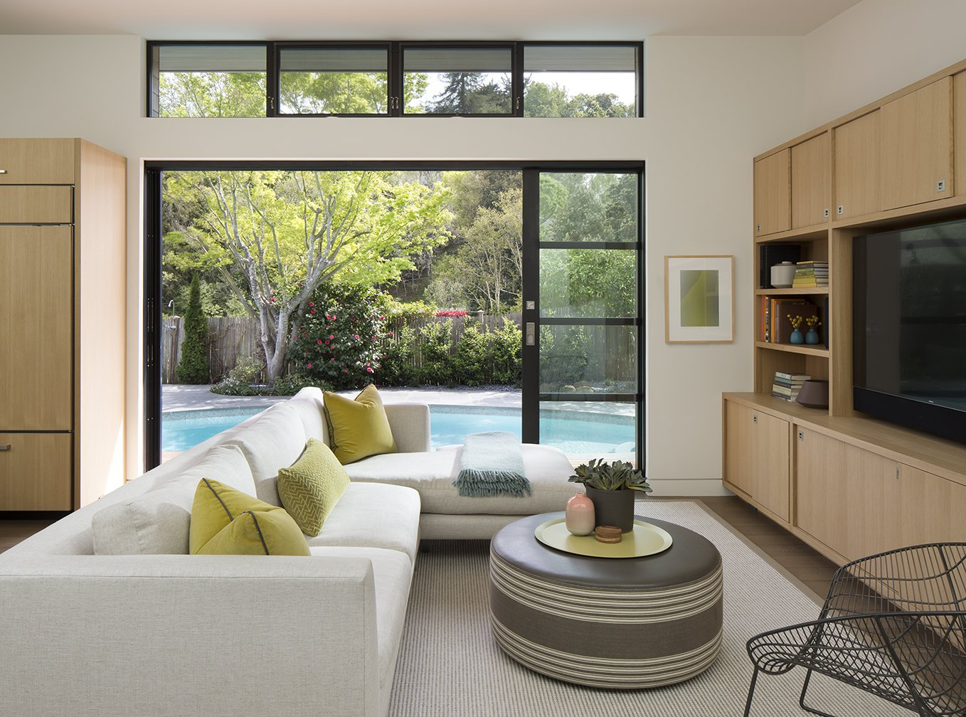 Sliding glass doors connect this renovated home in Marin County to a rear terrace and kidney-shaped pool.  Photo 2 of 5 in A New Spin on the Suburbs in Marin