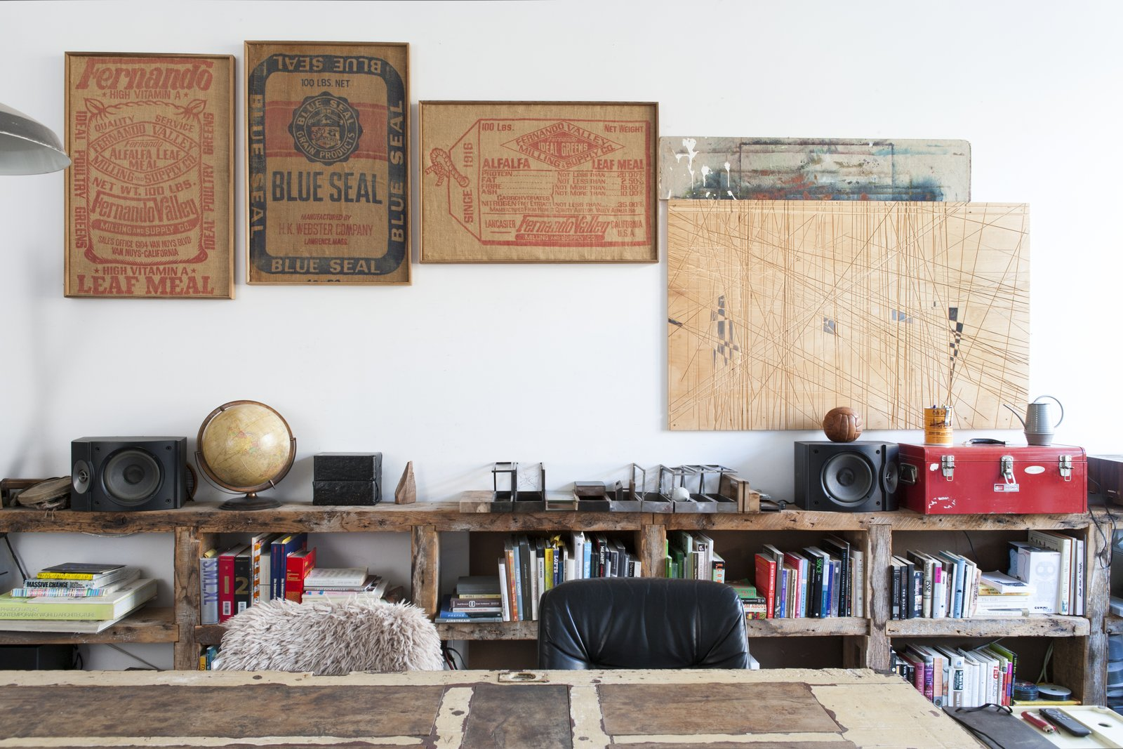 Office, Desk, and Study Room Type New York designer/artist Huy Bui decorated his home with a mishmash of curios, from 19th-century burlap sacks found at an antique fair to a plywood workbench he carved with a Festool plunge saw. The 17-foot-long shelving is made of old heart pine fashioned from the beams of brownstone renovation in the West Village.  Photo 2 of 5 in Huy Bui's Brooklyn Loft Is Like a Self-Contained Jungle