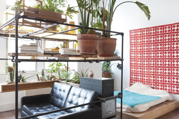 A platform bed is tucked behind a small living nook with a sofa and projector.