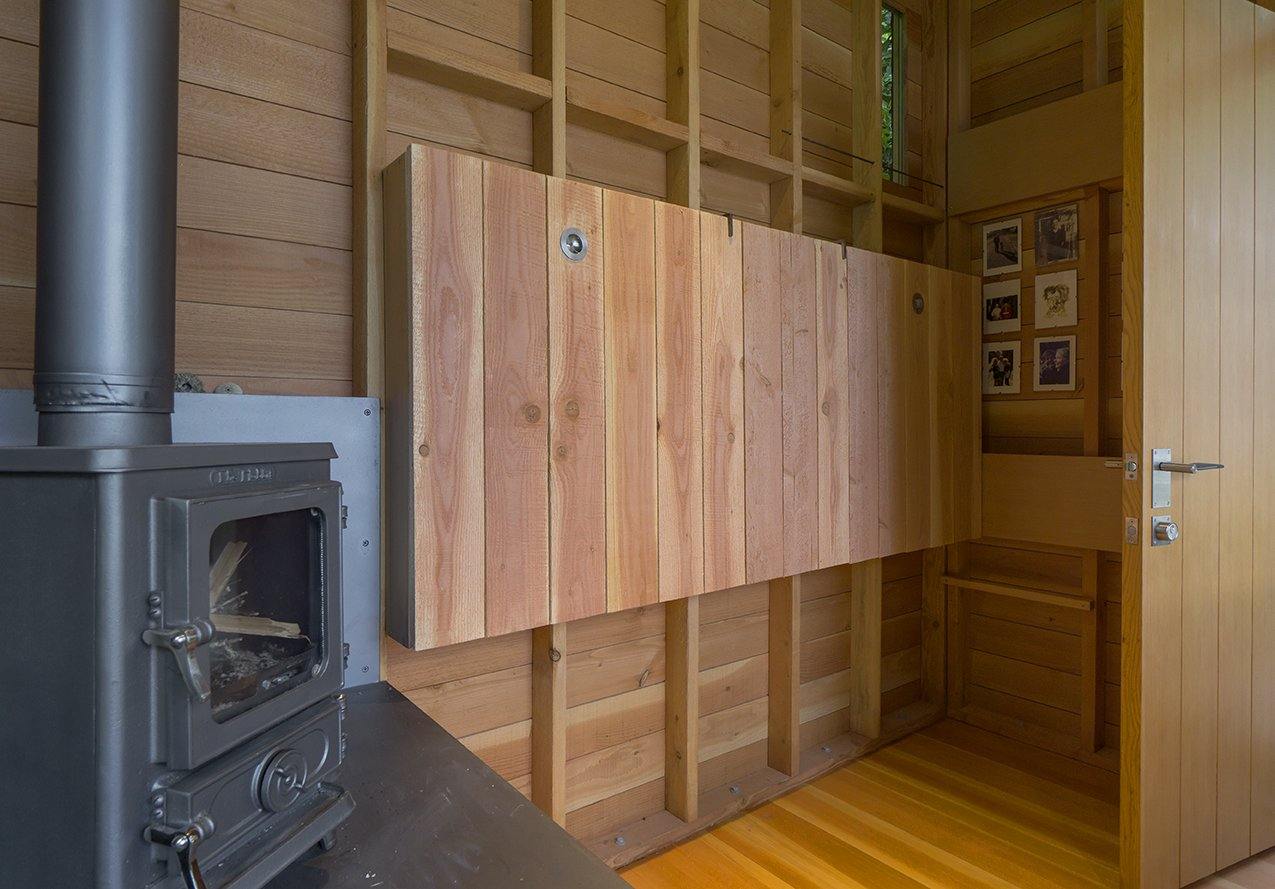 Shed & Studio, Living Space, Living Room, Den, and Family Room Outfitted with Woolrich linens and pillows designed by Jim's wife, Beth Wheeler,  the bed is wall-mounted with a hinge from McMaster Carr, so it can be folded up when not in use.  Shed & Studio Family Room Photos from An Architect and His Preteen Daughter Built This Tiny Backyard Retreat Together