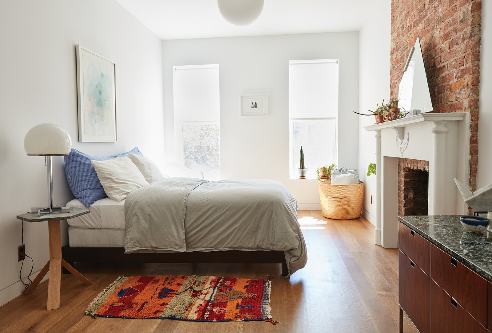 """Bedroom, Pendant, Bed, Table, and Medium Hardwood """"We put a lot of energy—and at least half our investment—into the bones of the building because we intend to be here for a long time,"""" says Lauren Snyder, who resuscitated an aging home alongside her husband, architect Keith Burns. They used simple, basic materials like plaster, brick, and wood throughout to keep it feeling honest, they said.  Best Bedroom Bed Pendant Table Photos from Forever Changes"""