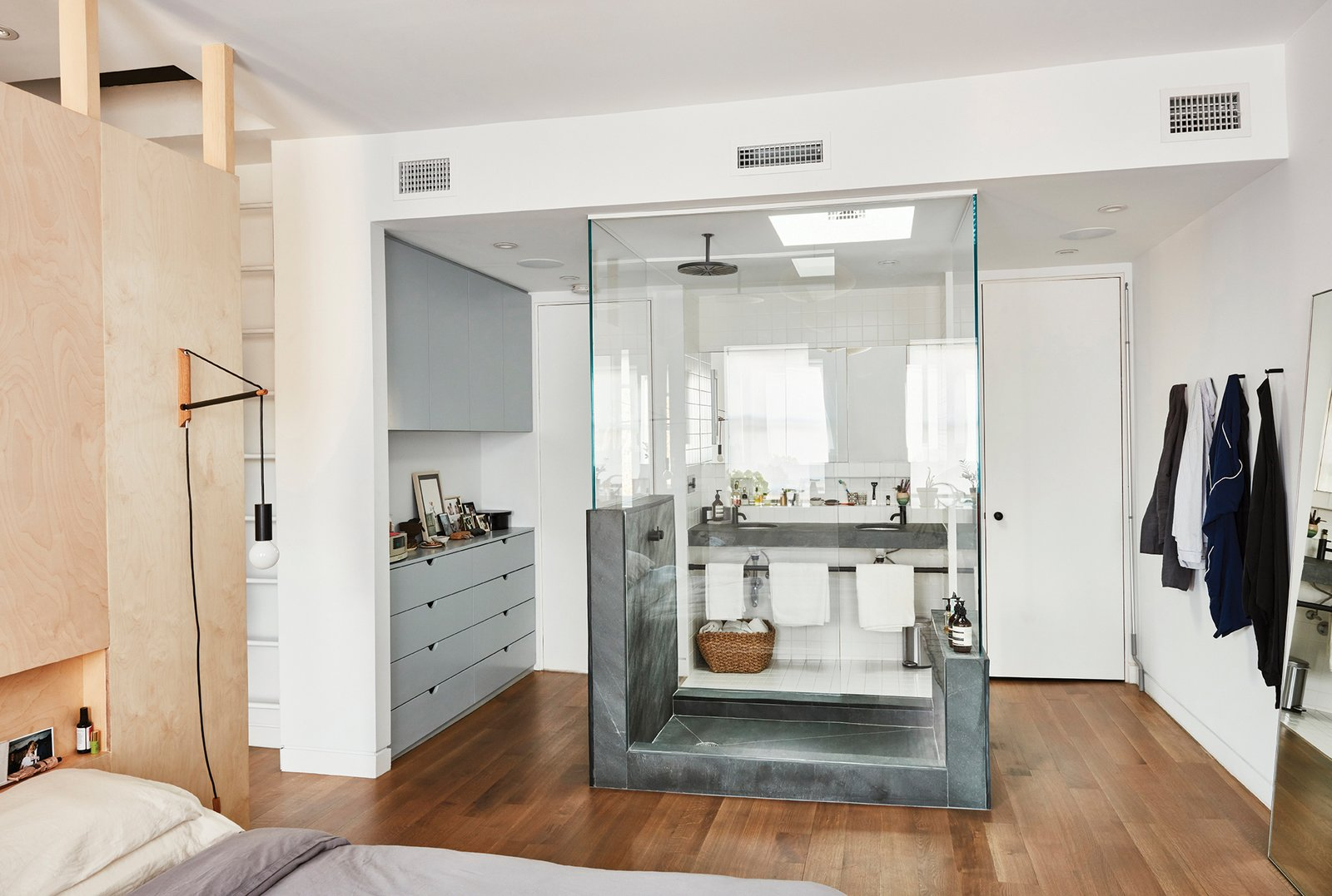 """Medium Hardwood, Bed, Bath, and Enclosed One of the boldest moves was the glass-encased shower inside the revamped master bedroom. """"Obviously, building that shower was not a cost-saving option,"""" says Keith, """"but we used green slate, which is not super expensive, either."""" The Architec sinks are from Duravit.  Best Bath Bed Enclosed Photos from Forever Changes"""