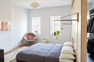 """Everything in the bedroom is built in, including the bed,"" adds Keith, who commissioned Hub Woodworks to mill this key feature. Andrew Neyer Crane lights flank the bed, an Akari pendant by Isamu Noguchi hangs overhead, and a Womb chair by Eero Saarinen for Knoll, covered in Cassia fabric from Designers Guild, sits in the corner."