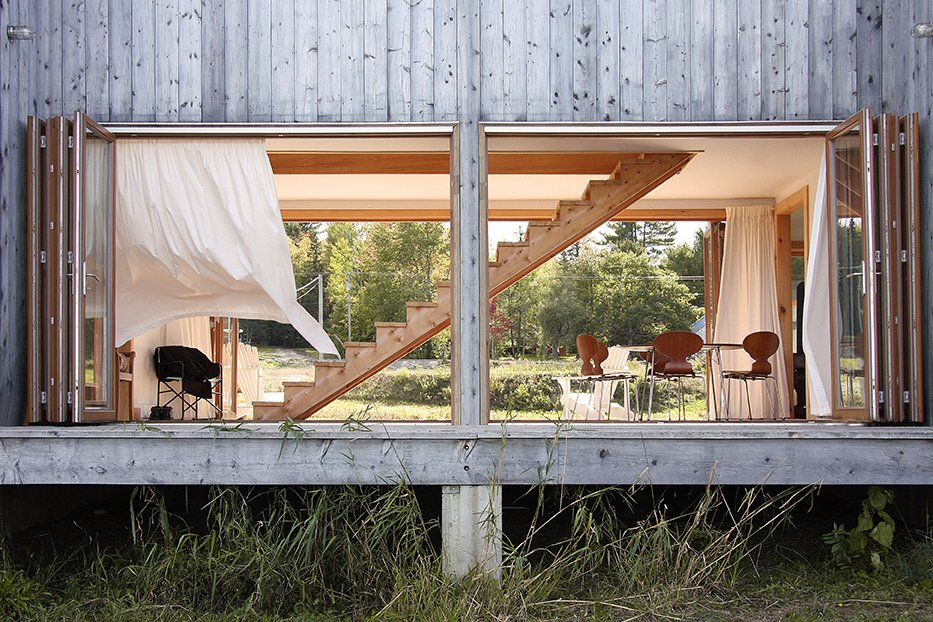 Architects Antje Freiesleben and Johannes Modersohn combined two barn-like wings and a large connecting hall/breezeway for a retreat in New Brunswick. A space between the concrete foundation and the house's raised wood platform allows the snowmelt to pass through in spring. The 21-foot-wide accordion doors are by HFBB Holzfensterbau Bernau and were shipped from Germany.  House R