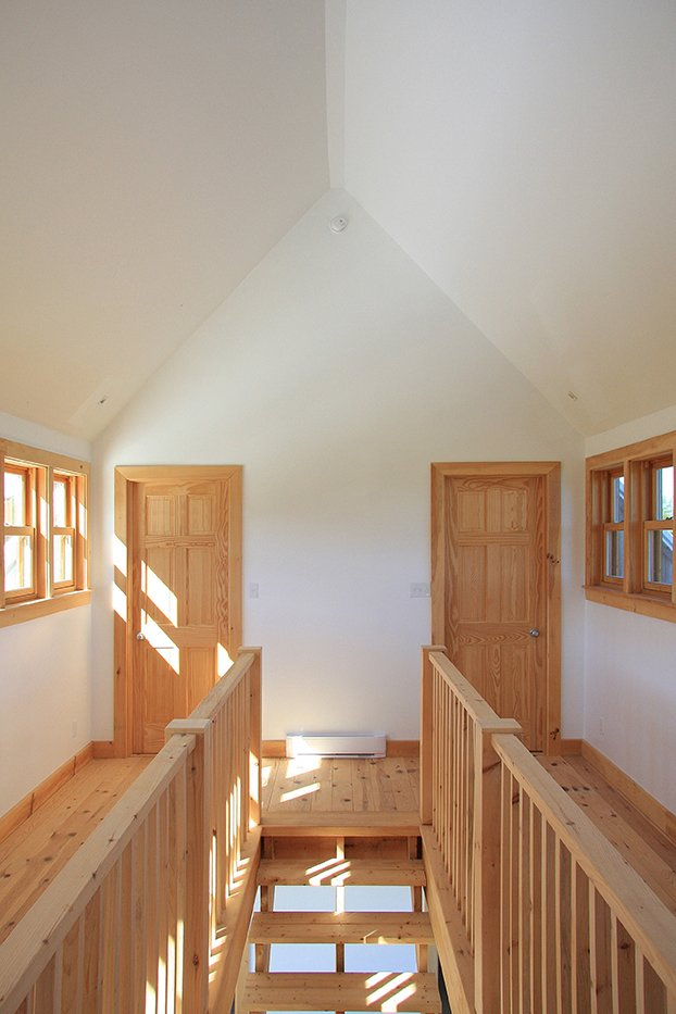Hallway and Medium Hardwood Floor Several types of wood were used to build the house, including red pine for the floors, white cedar for the porch, and black spruce for the siding.  House R from Barn Raising