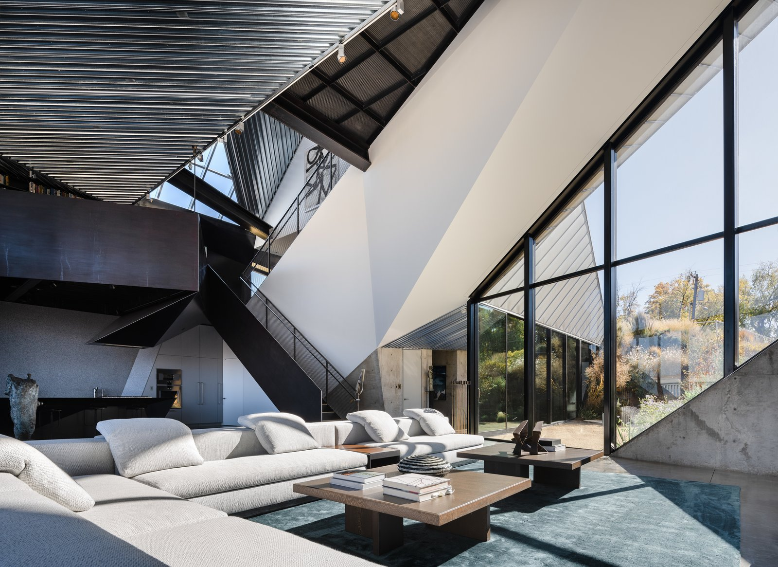 Living Room, Sectional, Rug Floor, Coffee Tables, Track Lighting, and Concrete Floor The Yang sectional and Dibbets rug are both from Minotti; the coffee tables are by  Eric Freyer.  Photo 7 of 19 in Two Art World Veterans Live in This Mind-Bending Metal Home in Nevada