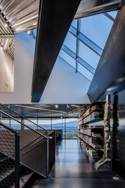 Sticking out above the kitchen, the triangular library showcases a sculpture by Stephen De Staebler.