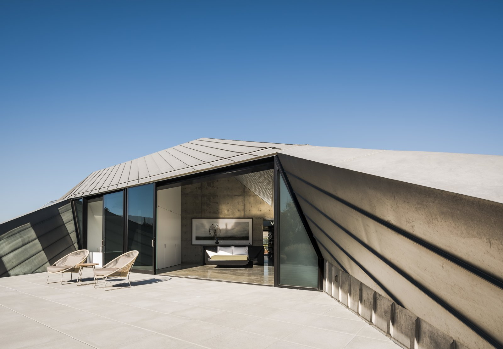 Outdoor, Large Patio, Porch, Deck, Rooftop, and Concrete Patio, Porch, Deck A cutaway in the standing-seam zinc roof creates an outdoor area for the guest suite. The chairs are from Teak Warehouse.  Photo 17 of 19 in Two Art World Veterans Live in This Mind-Bending Metal Home in Nevada