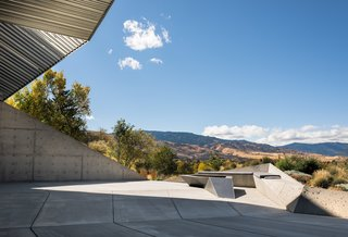 A concrete patio, accessible by large sliders, flows into the landscape.