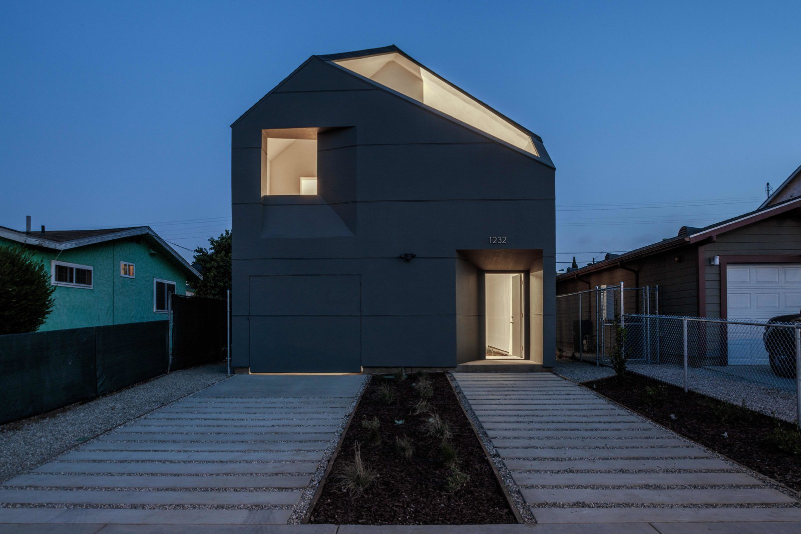 The new house stands out in the neighborhood, illuminated at night.  Photo 8 of 9 in When Building a House Is the Ultimate Final Exam