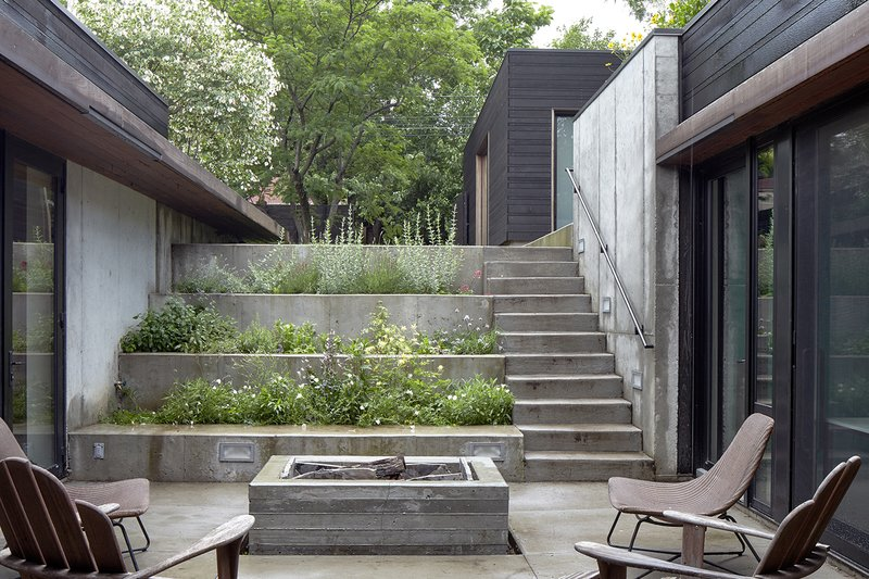 A stepped concrete garden planted with herbs and flowers marks the descent to the house. The courtyard is the focal point of the U-shaped structure; there is clear visibility between the kitchen on one side and the children's bedrooms on the other.  outdoor spaces from House of the Week: A Striking Slope
