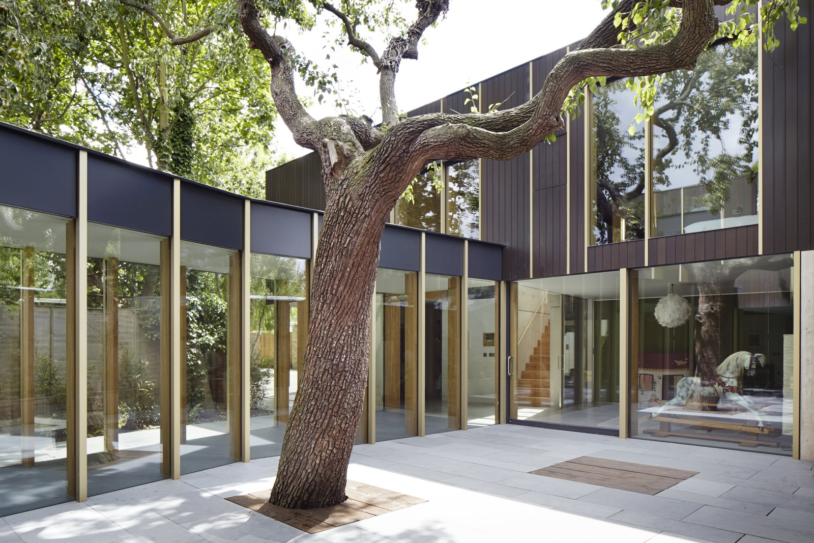 "Outdoor, Concrete Patio, Porch, Deck, Pavers Patio, Porch, Deck, and Trees ""I believe that the beauty is in the execution. Beautiful things can be made from humble materials with thought and care,  Photo 2 of 9 in This Modern Courtyard Home Celebrates a 100-Year-Old Tree"