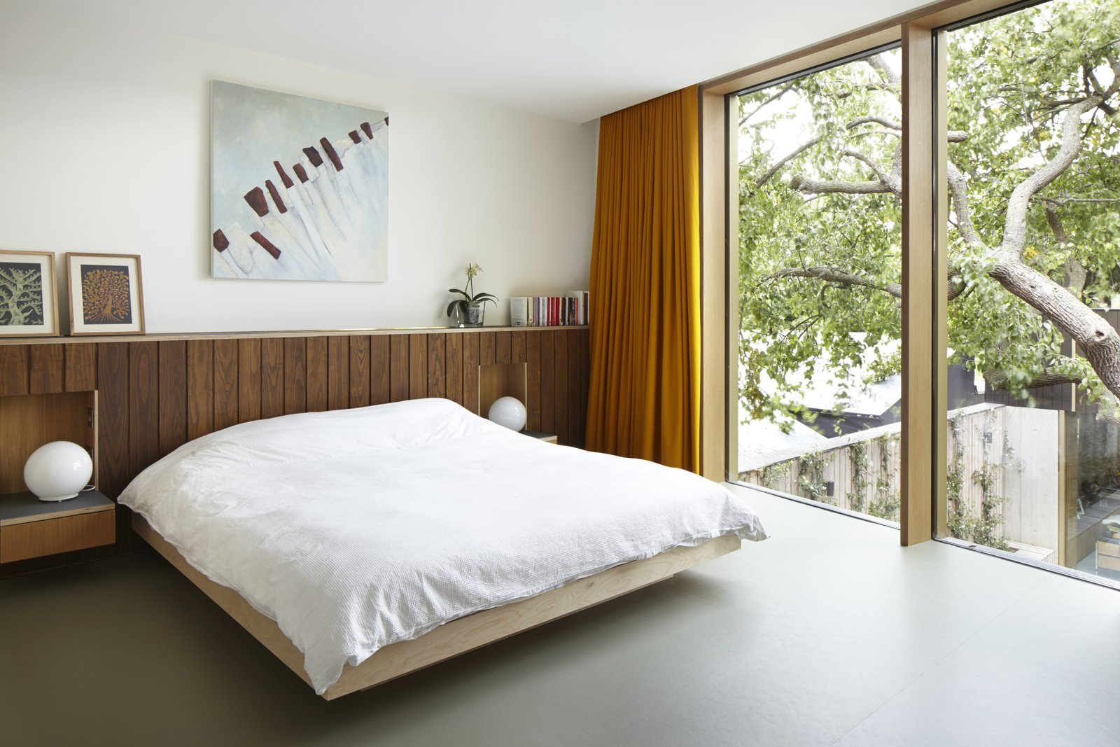 Bedroom, Bed, and Concrete Floor Edgley Design designed the beds and headboards in the bedrooms. Just one of the several bespoke details that the firm included in the home.  Photo 9 of 9 in This Modern Courtyard Home Celebrates a 100-Year-Old Tree