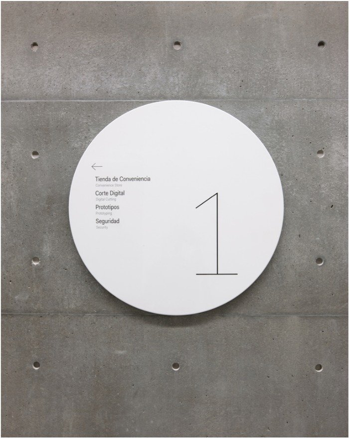 Identification and wayfinding signage appears on shiny metal discs that stand in contrast to the building's textured concrete walls.  Way-Finding Systems