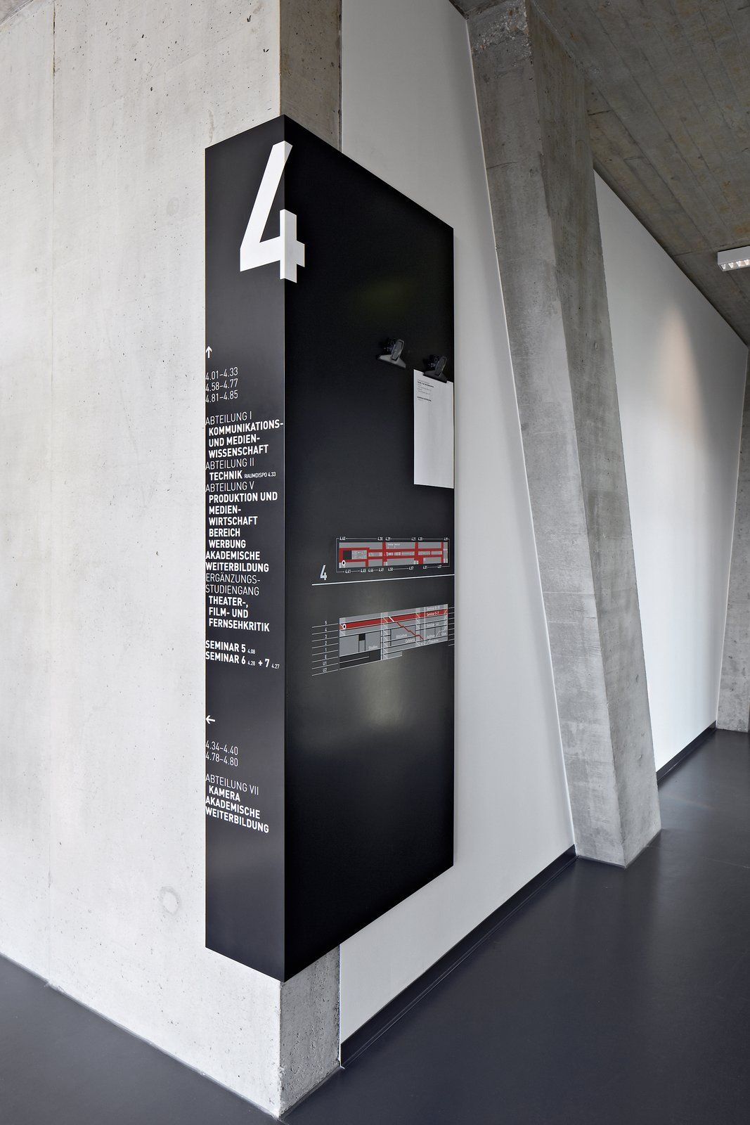 University of Television and Film Munich: More detailed information is contained on distinctively designed black signs that wrap around corners almost like shadows, so that they can be easily seen from the floors and the central staircase.  Way-Finding Systems