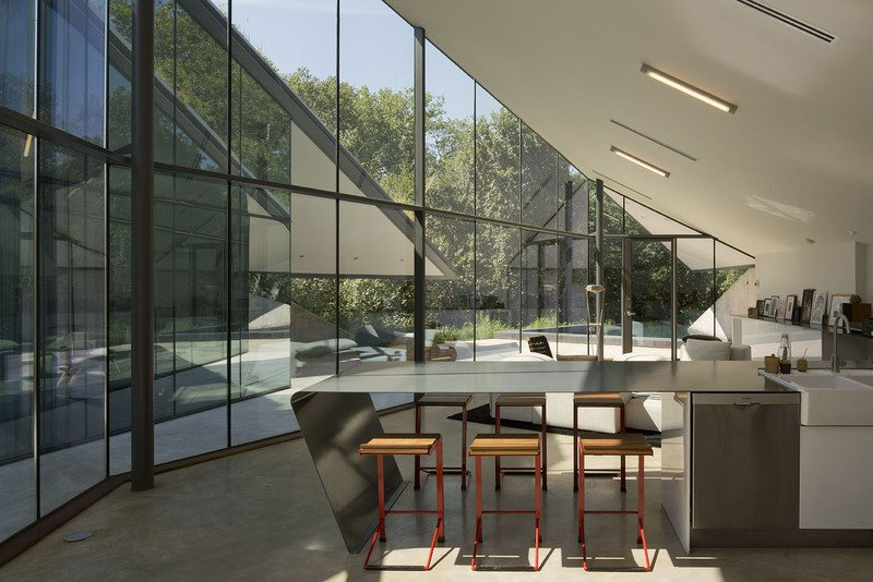 #EdgelandHouse #residence #modern #sunken #pithouse #interiors #windows #glass #lighting #counter #barstools #inside #indoors #structure #BercyChenStudio  Edgeland House by Bercy Chen Studio
