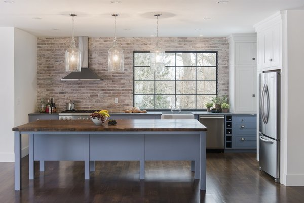 Kitchen, White, Wood, Brick, Dishwasher, Dark Hardwood, Drop In, Refrigerator, Range Hood, Pendant, Range, and Recessed This beautiful Arlington kitchen by Pinney Designs features a Marvin Contemporary Direct Glaze window with contrasting black painted interior to set off the industrial brick wall.   Design: Pinney Designs  Photo: Ben Gebo  #industrial #butcherblock #marvin #kitchen  Best Kitchen White Dishwasher Pendant Wood Photos from Light-Filled Kitchens