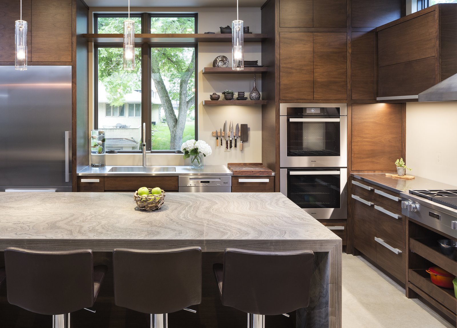 Kitchen, Wood Cabinet, Pendant Lighting, Refrigerator, Wall Oven, Range, Range Hood, and Dishwasher Builder John Kraemer & Sons' Lake Calhoun Organic Modern residence, winner of 2016 Integrity Red Diamond Achiever Award  Lake Calhoun Organic Modern