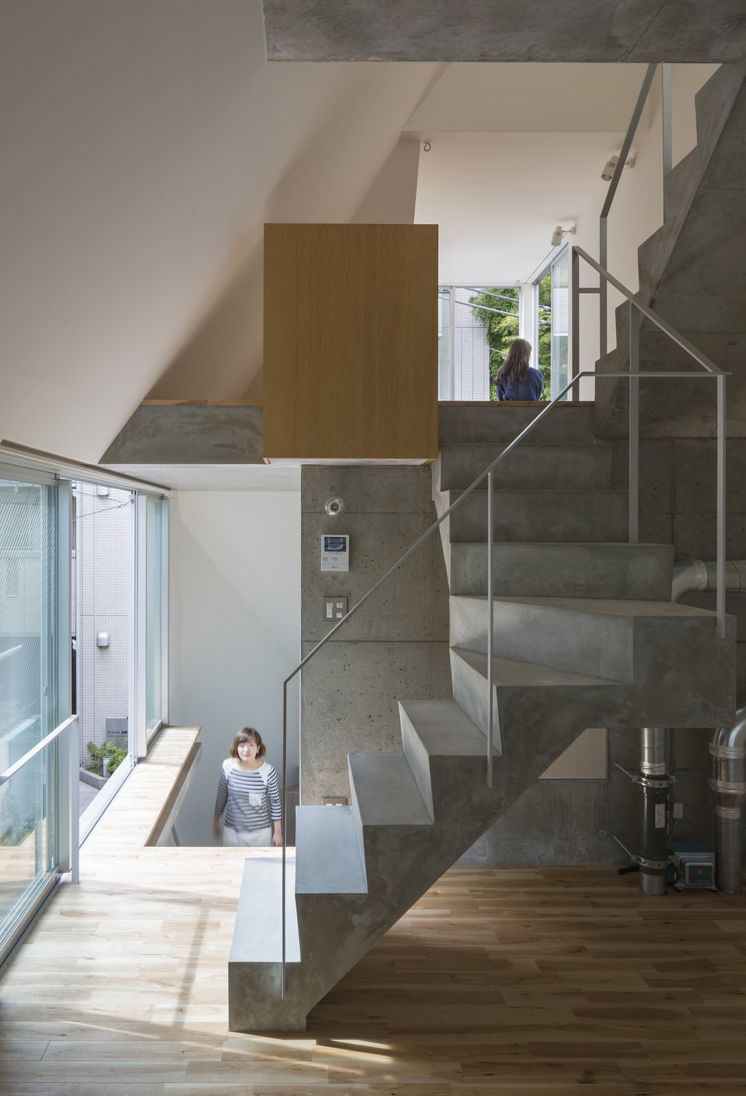 Staircase, Concrete, and Metal House in Tokyo is a minimal residence designed by Ako Nagao + miCo for a couple who required a music studio. The site is located between reinforced concrete mid-to-high-rise apartments and an old wooden housing area. The volume needed to be closed and  Best Staircase Photos from House in Tokyo by Ako Nagao + miCo